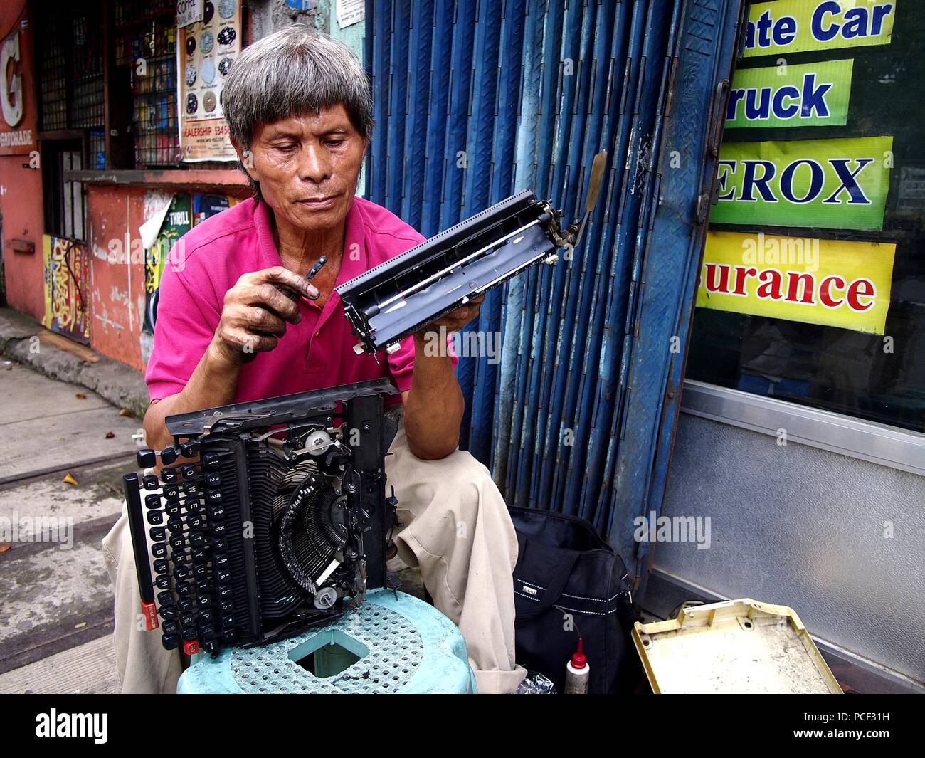 ANTIPOLO CITY, PHILIPPINES - JULY 30, 2018: A repairman fixes an old manual typewriter at a sidewalk along a busy street. Stock Photo