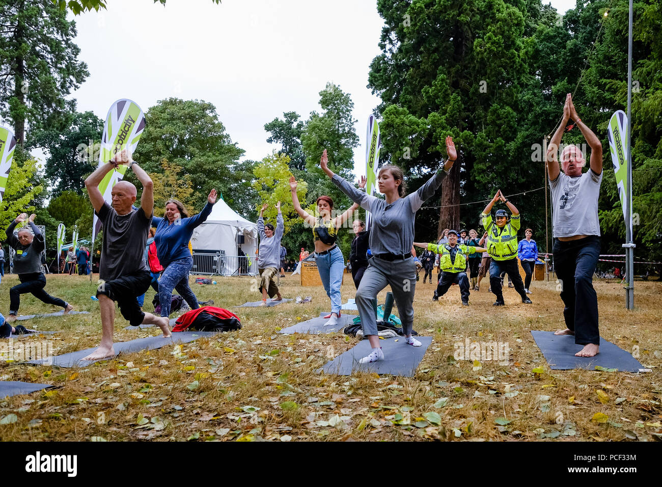 Police join a Yoga Class at WOMAD on Sunday 29 July 2018 held at Charlton Park, Wiltshire . Pictured: 2 Police officers of the Wiltshire Police Force joined in a free Yoga Class taking place in the World of Wellbeing . - Stock Image