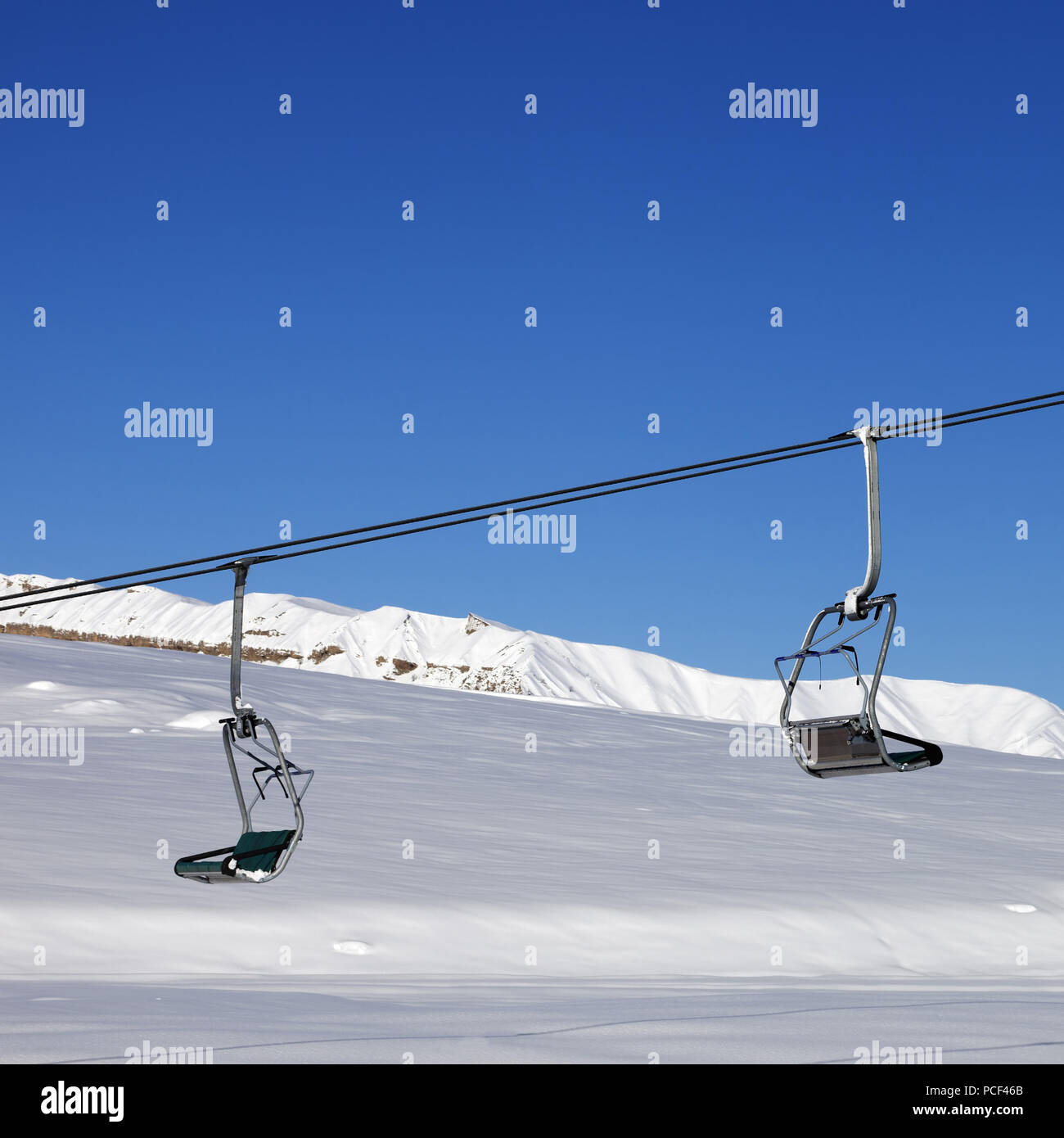 Chair-lift and blue clear sky at sun day  Caucasus Mountains