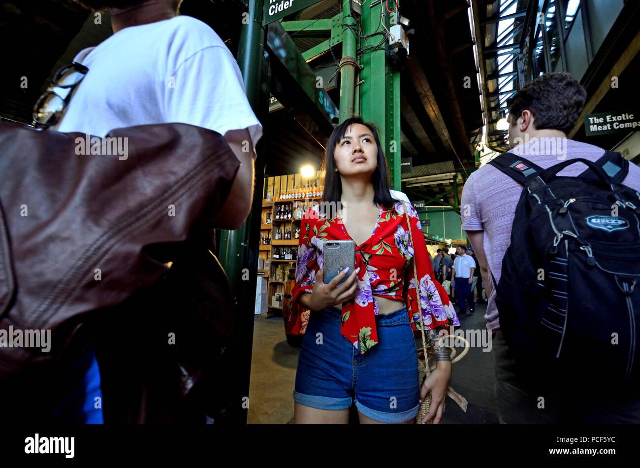 Asian tourist in a crowded Borough Market, Southwark, London, England, UK. Stock Photo