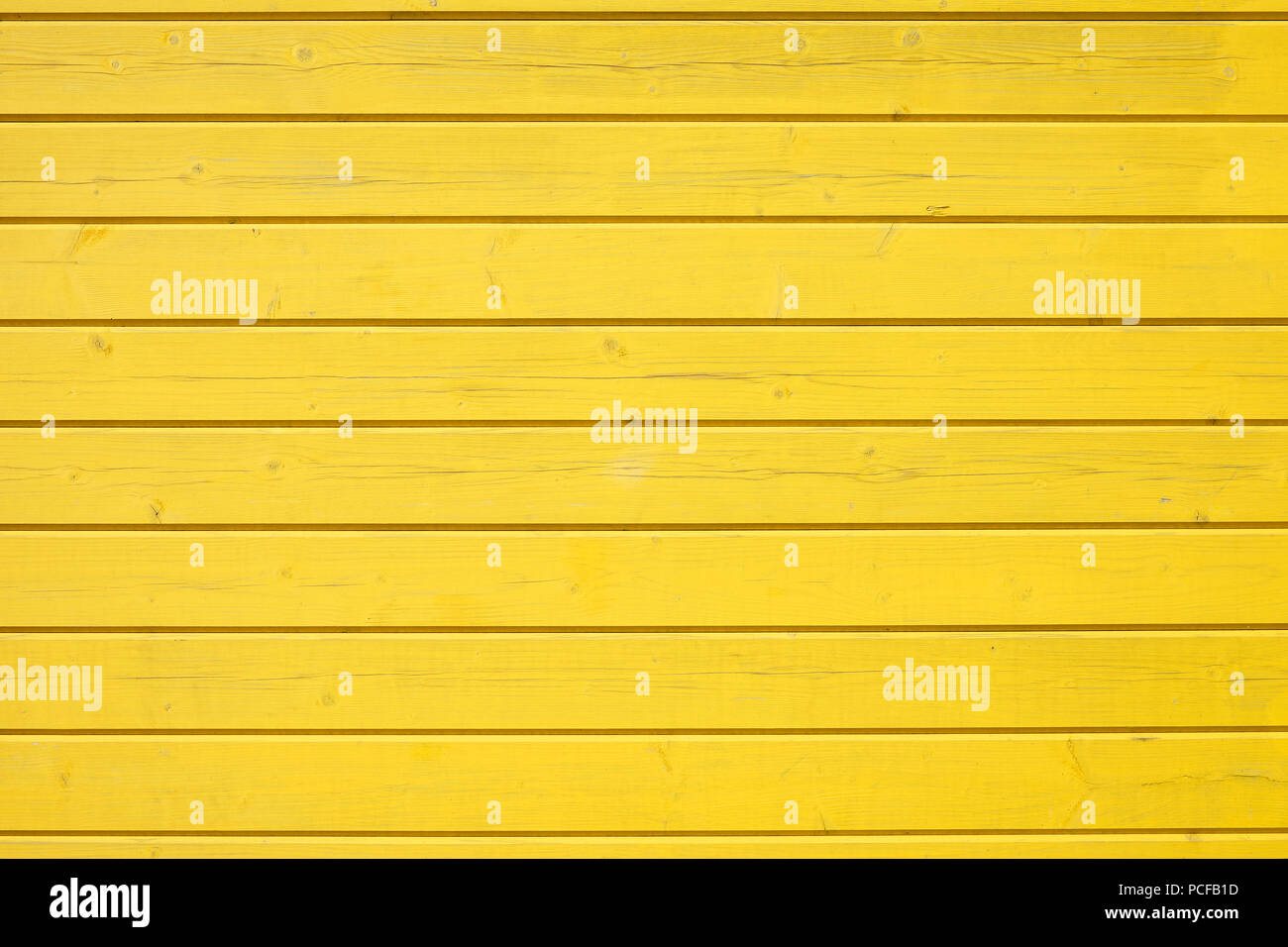 Wooden wall of horizontally arranged yellow painted boards, background image - Stock Image