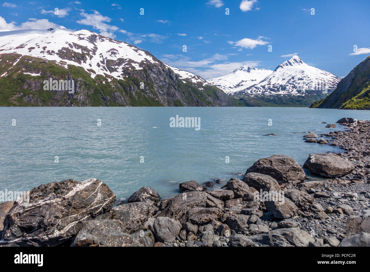 Snow capped mountains around Portage Lake which  is a glacial lake in the Chugach National Forest on the Kenai Peninsula of Alaska - Stock Image