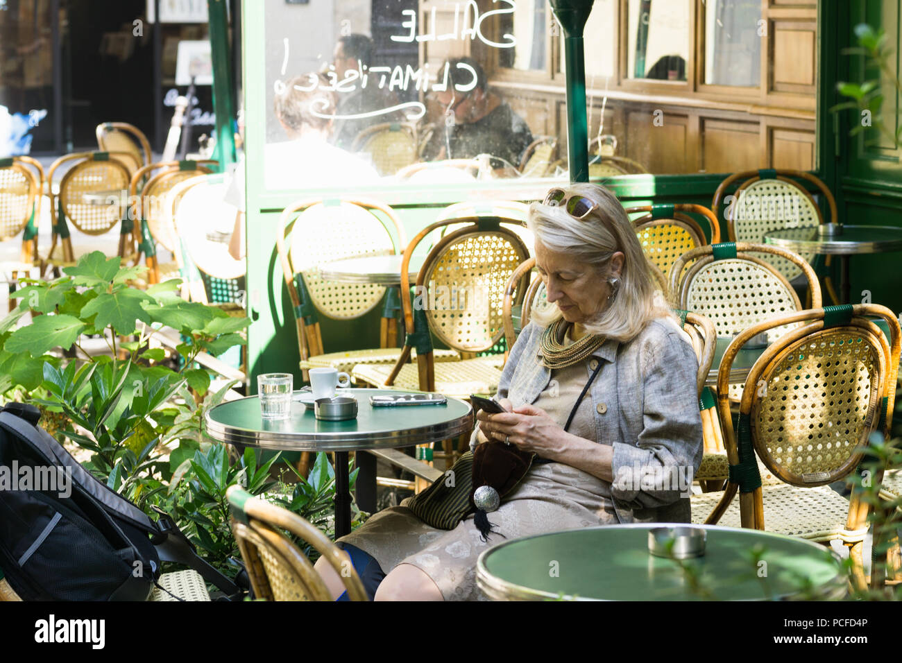 Parisian Woman Checking Her Phone And Drinking Coffee At La Chaise
