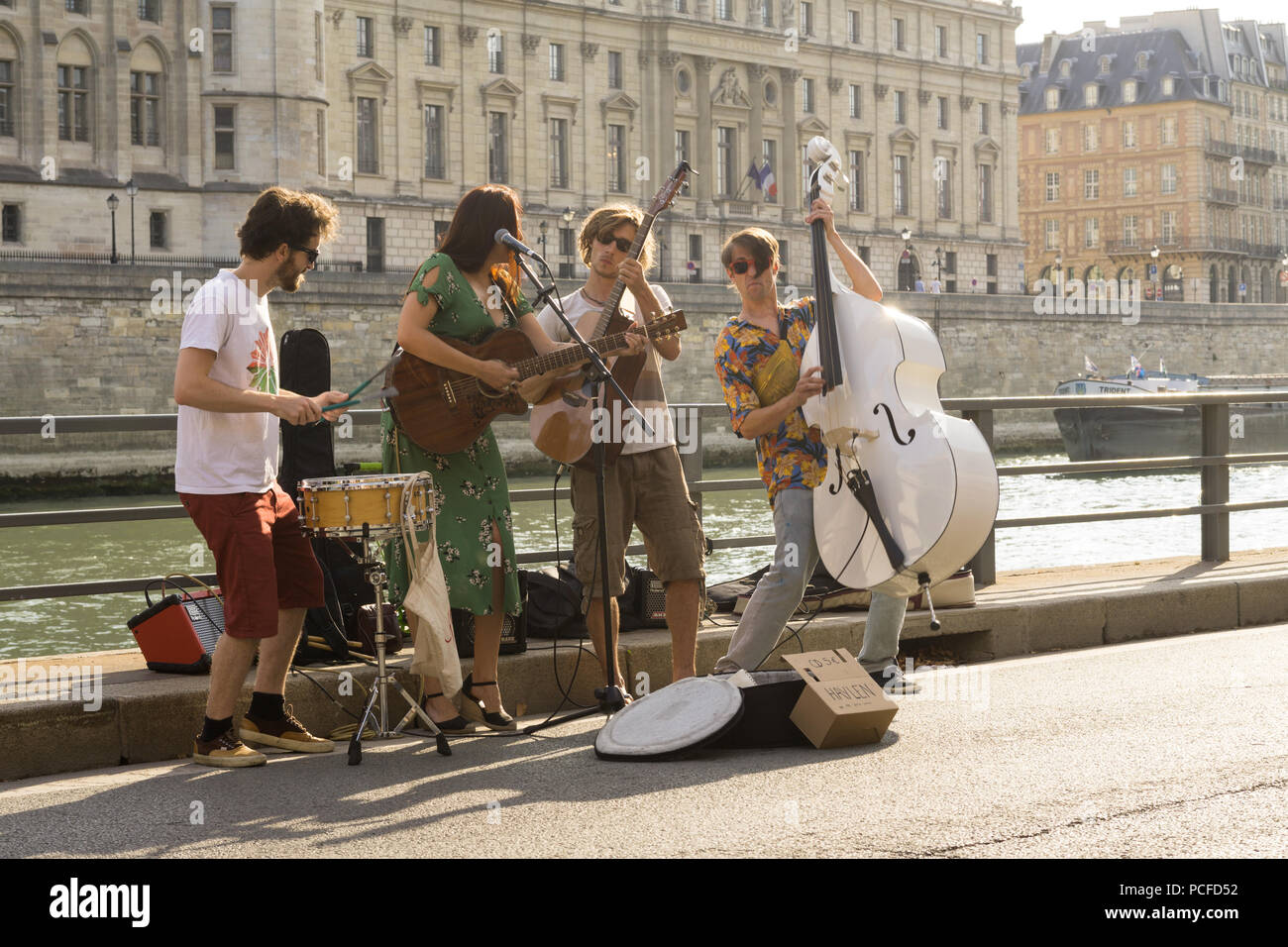Street musicians playing at the embankment of the Seine River in Paris, France. - Stock Image