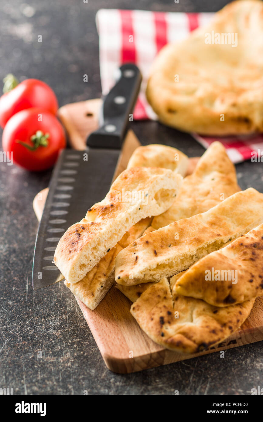 Indian naan bread on old kitchen table. - Stock Image