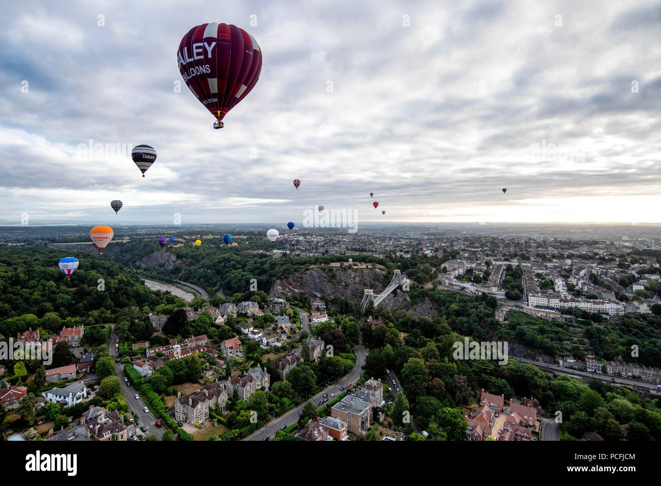 Hot air balloons above the Clifton Suspension Bridge during the press launch for the Bristol International Balloon Fiesta. - Stock Image