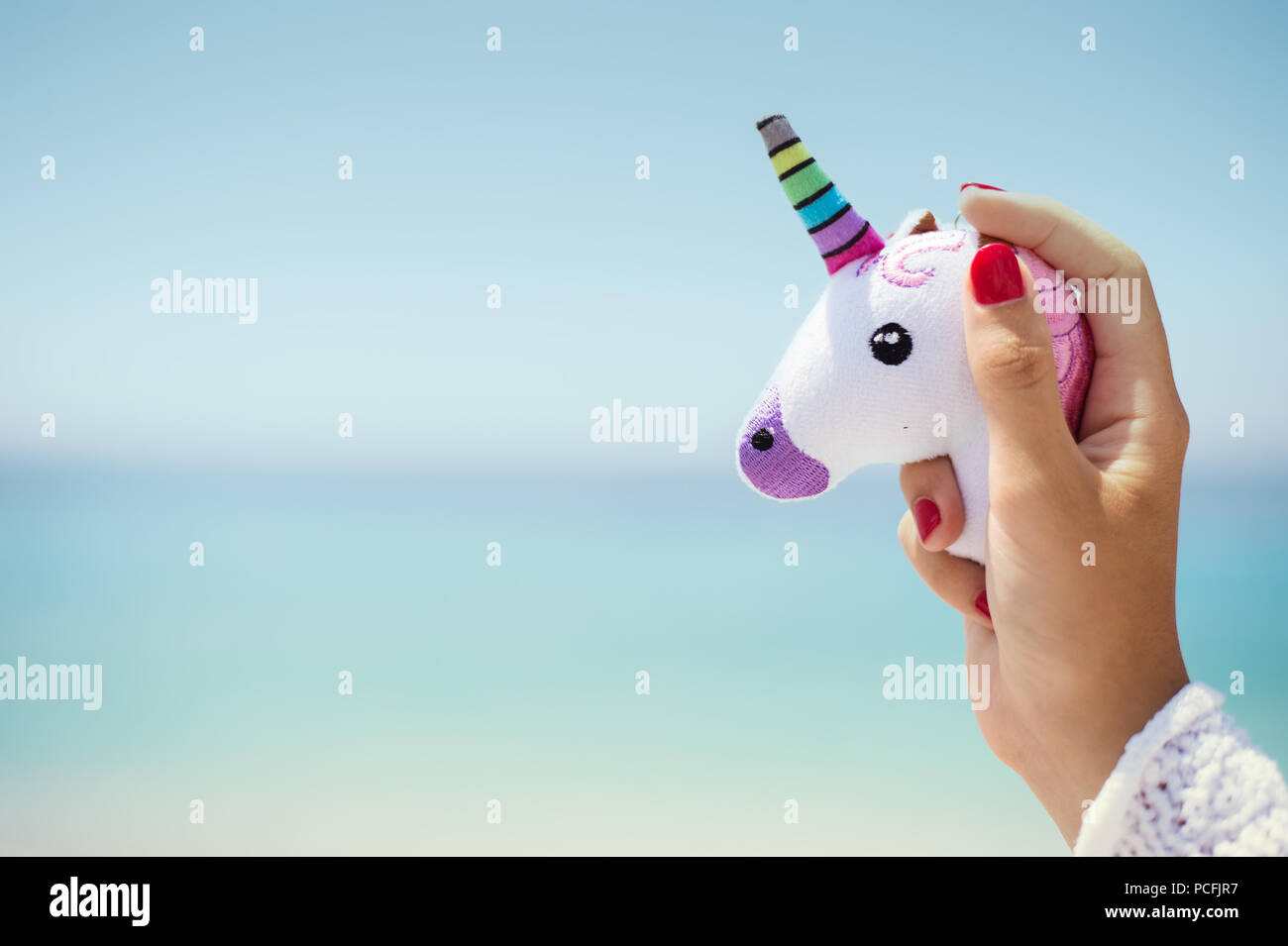 Hand holding pink trendy unicorn on blue sky background. Empty space. - Stock Image