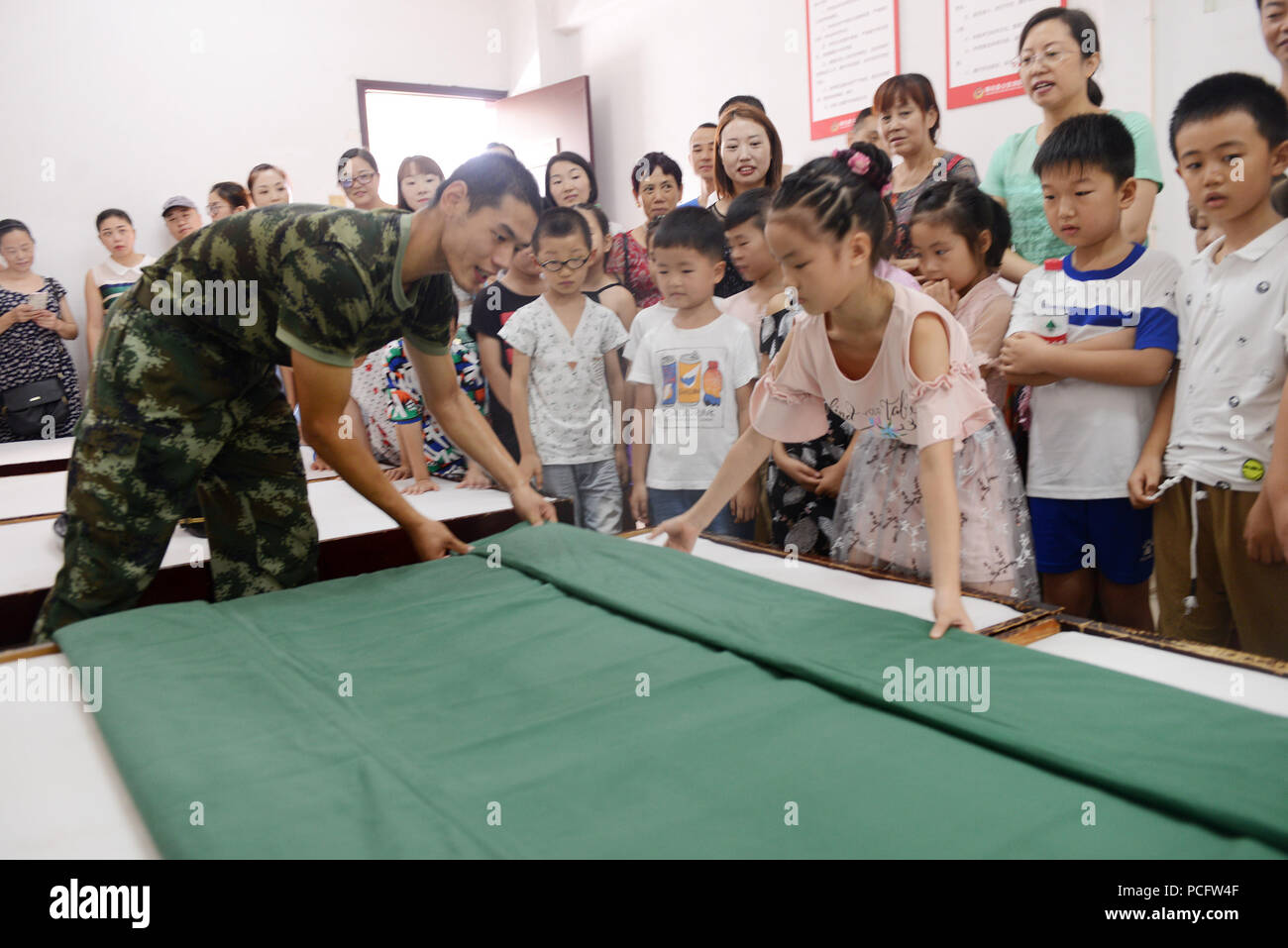 Zigui, China's Hubei Province. 2nd Aug, 2018. Pupils accompanied by their parents learn to fold up an army quilt at Zigui County Fire Squadron in Yichang City, central China's Hubei Province, Aug. 2, 2018. Children participate in various activities to enrich their summer vacation. Credit: Wang Huifu/Xinhua/Alamy Live News - Stock Image