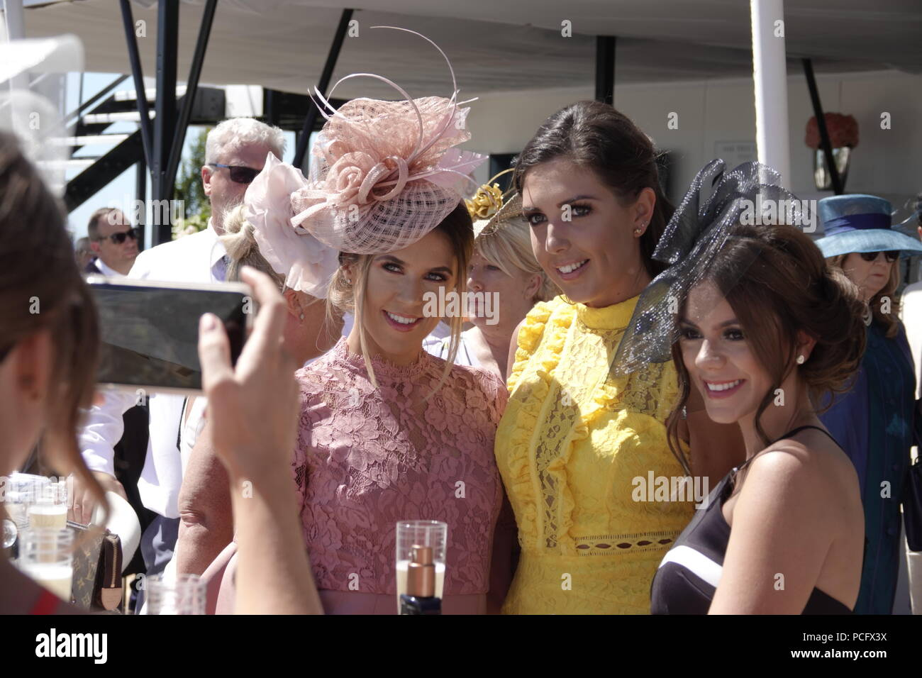 Goodwood Racecourse, West Sussex, UK. 2nd August,  2018   Goodwood Racecourse, West Sussex, UK The girls all dolled up take their 'selfies' during  Ladies Day on the sunny Sussex Downs at Glorious Goodwood day} three. Credit: Motofoto/Alamy Live News - Stock Image