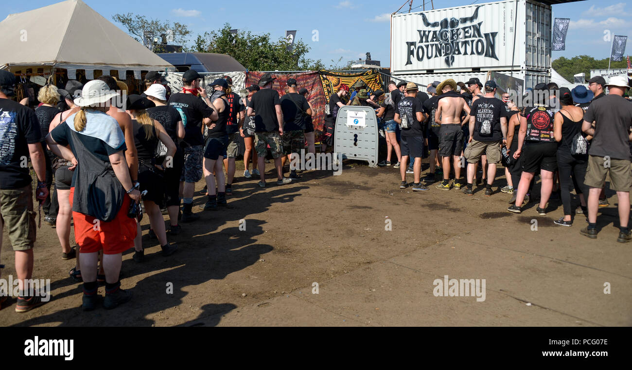 Wacken, Germany. 02nd Aug, 2018. Festival visitors stand in line for drinking water at the Wacken Open Air. According to the organisers, the world's largest heavy metal festival starts with 75,000 visitors. Credit: Axel Heimken/dpa/Alamy Live News - Stock Image