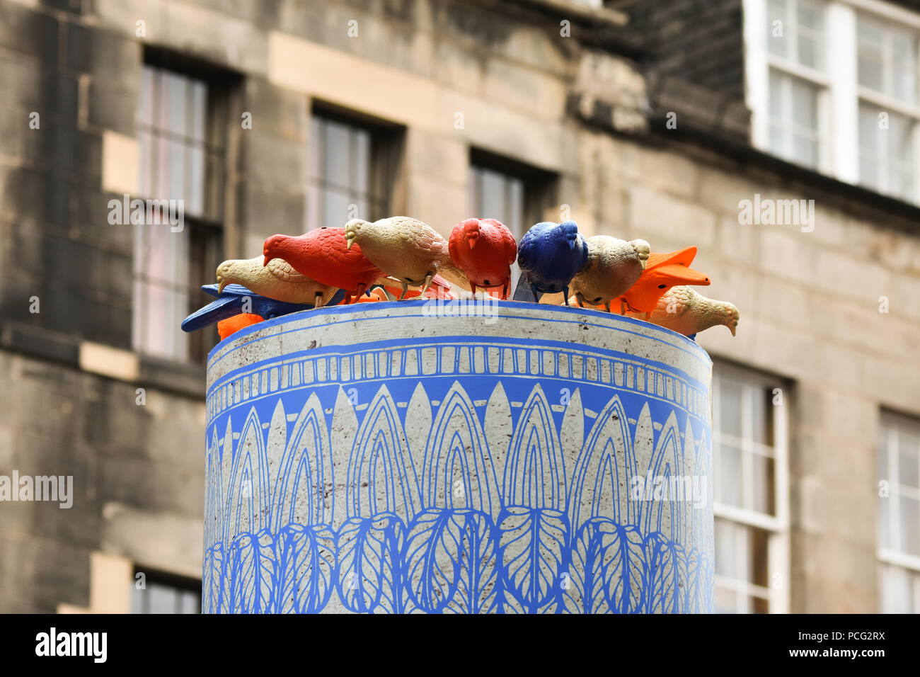 Edinburgh, UK. 2nd August, 2018, colourful plastic pigeons look on in Edinburgh's High Street at the start of the Festival Fringe season. Credit: George Philip/Alamy Live News - Stock Image