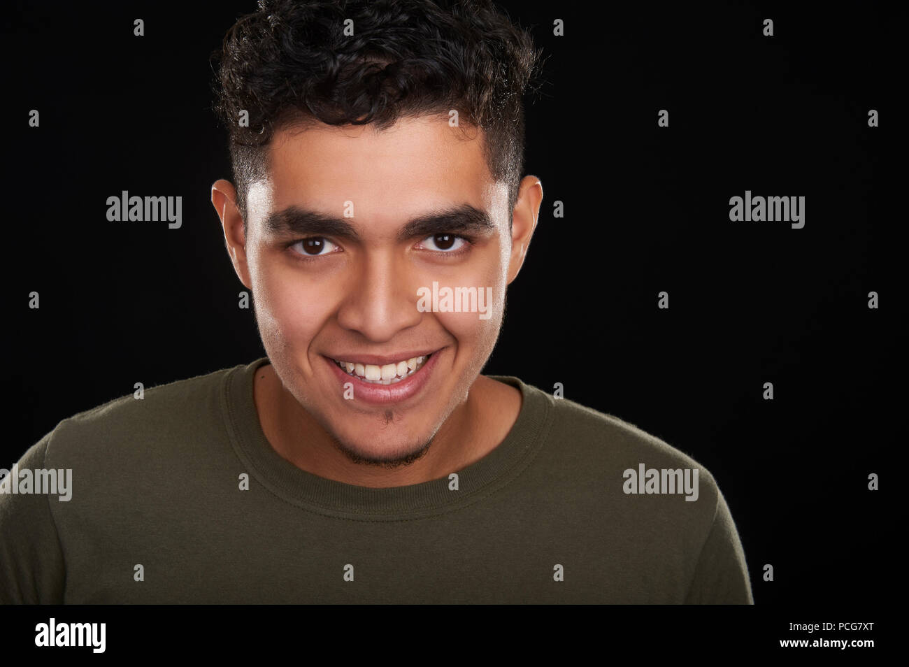 Studio portrait of a 19 years old young man, smiling - Stock Image