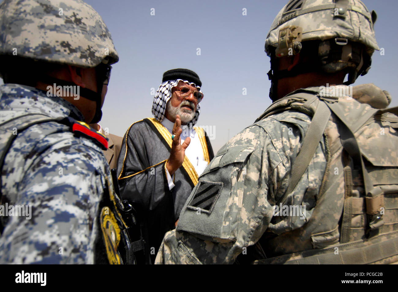 Abu Sabah, center, a respected elder, speaks to U.S. Army Lt. Col. Johnnie Johnson, right, assigned to the Personal Security Detachment, 4th Battalion, 64th Armor Regiment, 3rd Infantry Division, and an Iraqi soldier, left, at the opening of a swimming pool in Risalah, Baghdad, Iraq, Sept. 18, 2008. - Stock Image