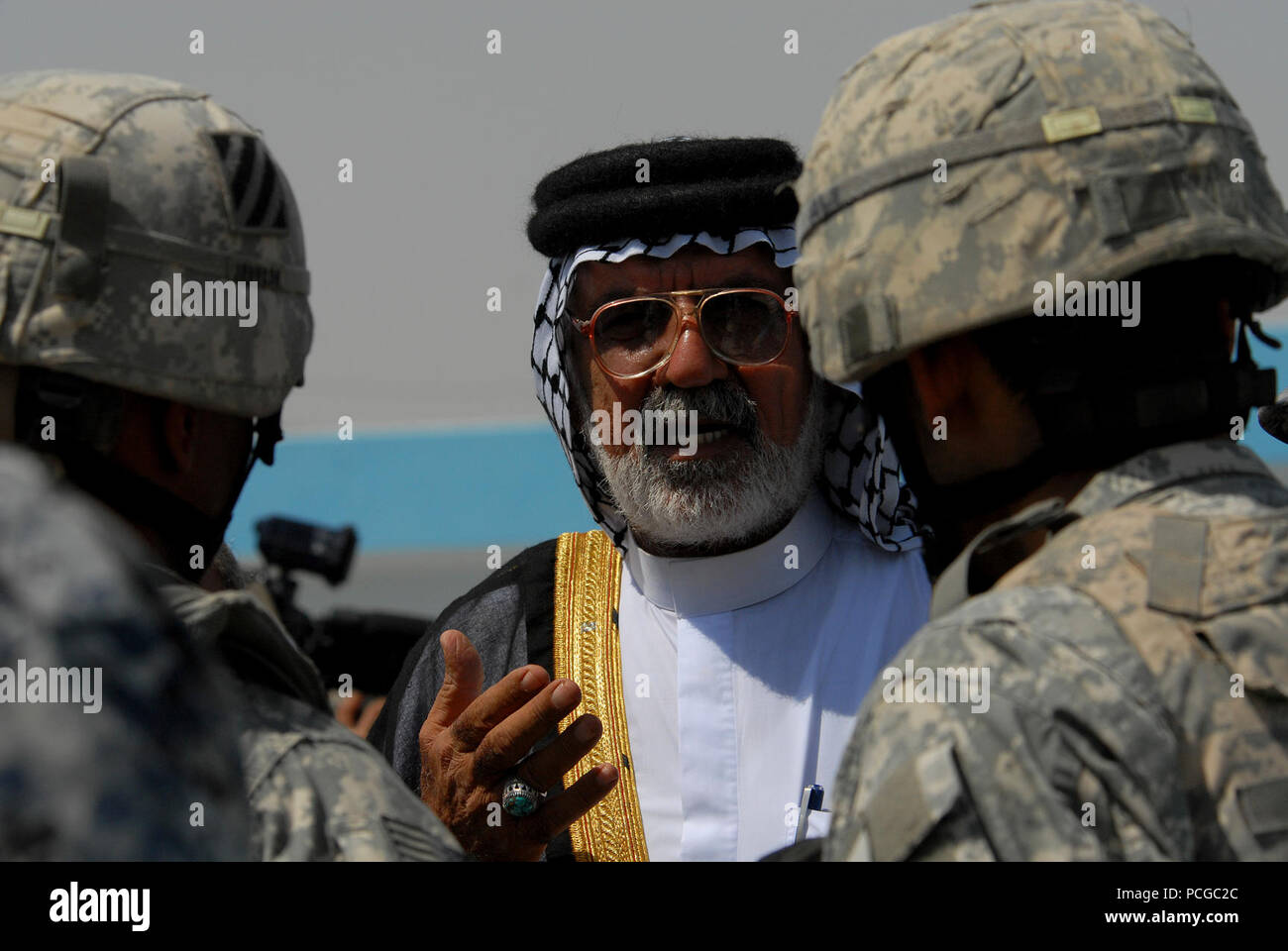 Abu Sabah, center, a respected elder, speaks to U.S. Army Lt. Col. Johnnie Johnson, right, assigned to the Personal Security Detachment, 4th Battalion, 64th Armor Regiment, 3rd Infantry Division, and another Soldier, left, at the opening of a swimming pool in Risalah, Baghdad, Iraq, Sept. 18, 2008. - Stock Image