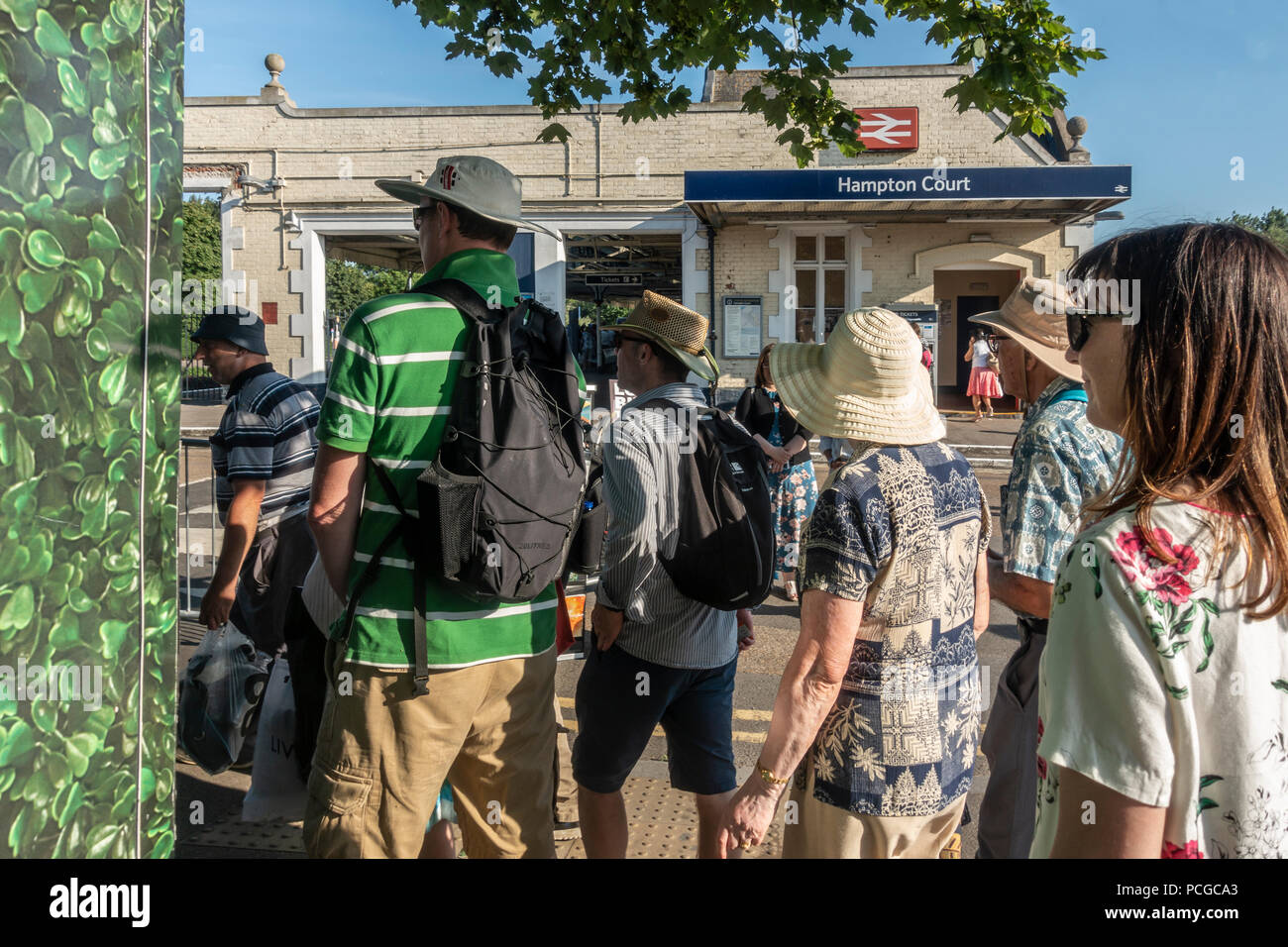 Passengers queueing for a train to London at Hampton Court station on a hot summer July day. East Molesey, Surrey, England - Stock Image
