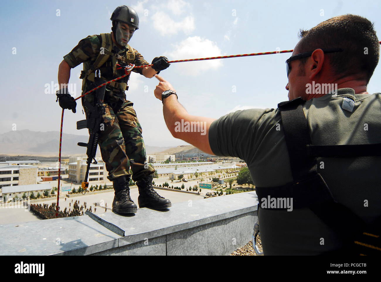 "KABUL, Afghanistan (August 9, 2010)  French Army Staff Sgt. Virion, right, an EPIDOTE program Afghan National Army (ANA) advisor, signals Afghan Captain Abdulhai, to begin a rappelling demonstration during a pre-Ramazan ceremony at Kabul Military Training Center (KMTC). ANA and visiting Coalition leaders watched security and quick response teams demonstrate their reactions to simulated insurgent attacks. Four ANA instructors at KMTC simulated a counterattack by firing blanks from the roof of a multi-story building, then rappelling down the side to aid in repelling the ""attackers."" (US Navy - Stock Image"