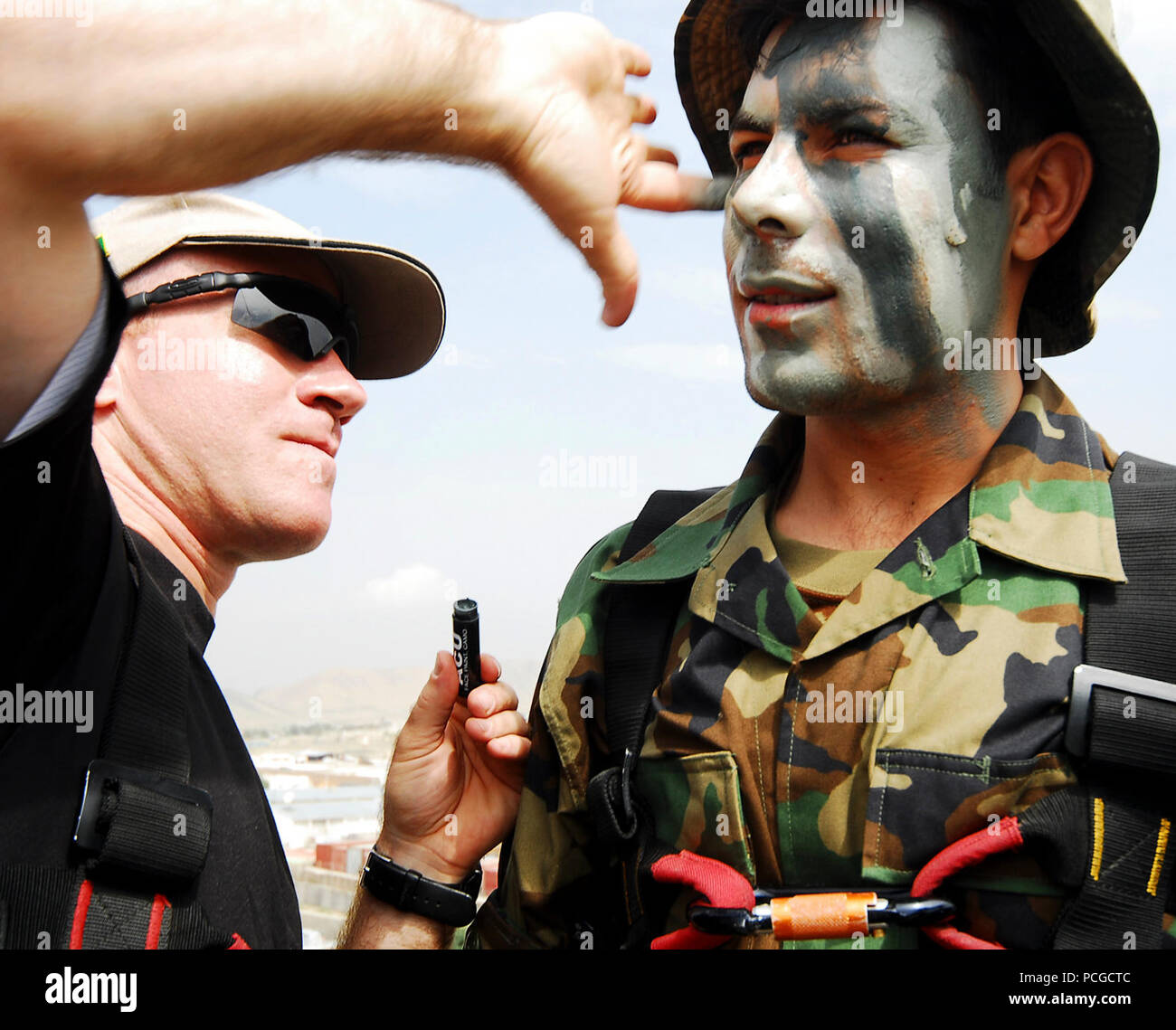 KABUL, Afghanistan (August 9, 2010)  French Army Captain Guillaume Quevarrec, left, an EPIDOTE program Afghan National Army (ANA) advisor, applies camouflage paint to the face of Afghan Captain Abdulhai, prior to a rappelling demonstration during a pre-Ramazan ceremony at Kabul Military Training Center (KMTC). ANA and visiting Coalition leaders watched security and quick response teams demonstrate their reactions to simulated insurgent attacks. Four ANA instructors at KMTC simulated a counterattack by firing blanks from the roof of a multi-story building, then rappelling down the side to aid i - Stock Image