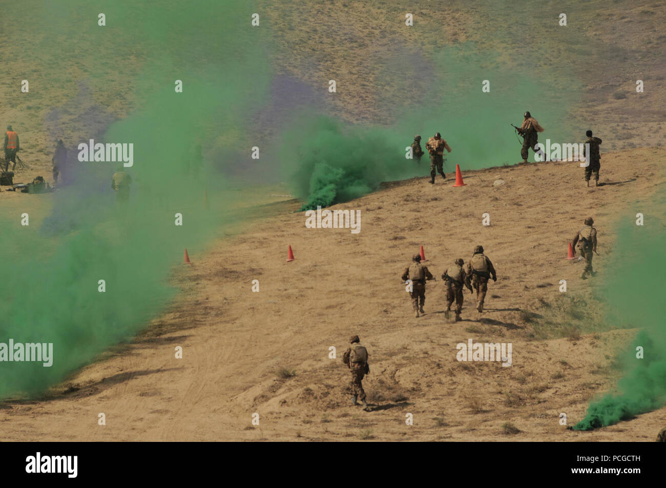 Afghanistan (September 2, 2010) – With colored smoke simulating the fog of war, Afghan National Army soldiers advance during a simulated strike on enemy positions at the Infantry Branch School in Darulaman. The school teaches Afghan soldiers infantry tactics and trains them on weaponry including mortars, crew-served weapons and recoilless guns. - Stock Image