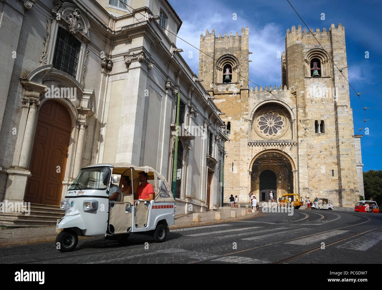 Lisbon. Tourists avoiding the steep climb by taking a Tuk-tuk. Cathedral Zé in the background. - Stock Image