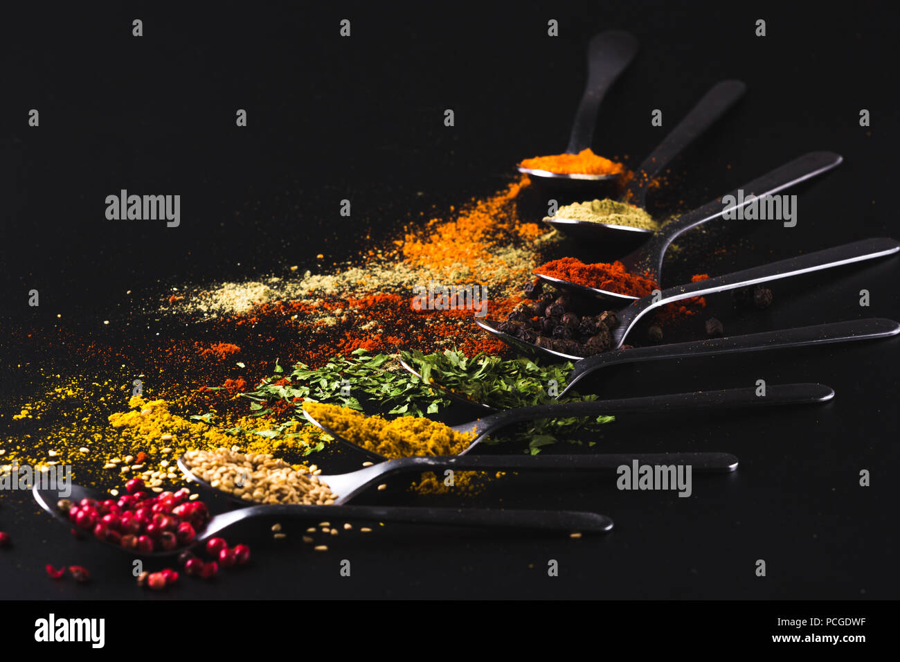 Composition of small spoons full of spices and condiments for cooking on a black background - Stock Image
