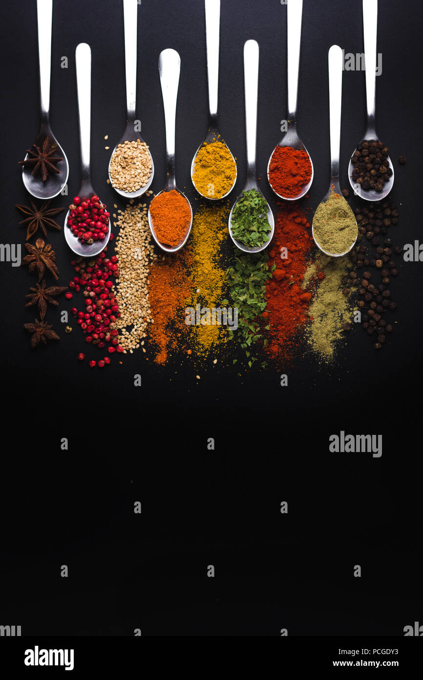 Spices and condiments for cooking on a black background, the image has a space available to add texts - Stock Image
