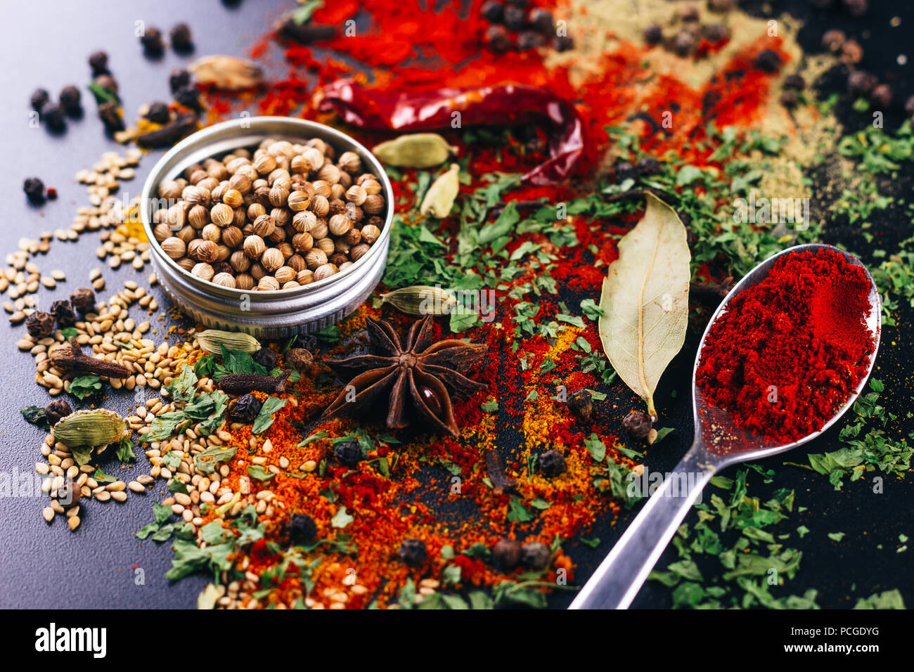 Disaster of spices and condiments for cooking, on a dark table, restaurant concept - Stock Image