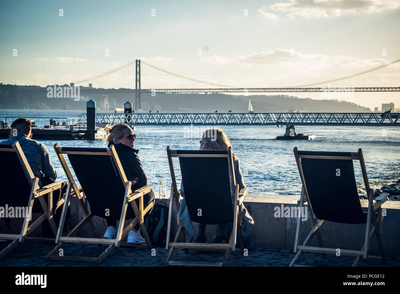 Lisbon. Peaple sitting in deck chairs by the river Targus. - Stock Image