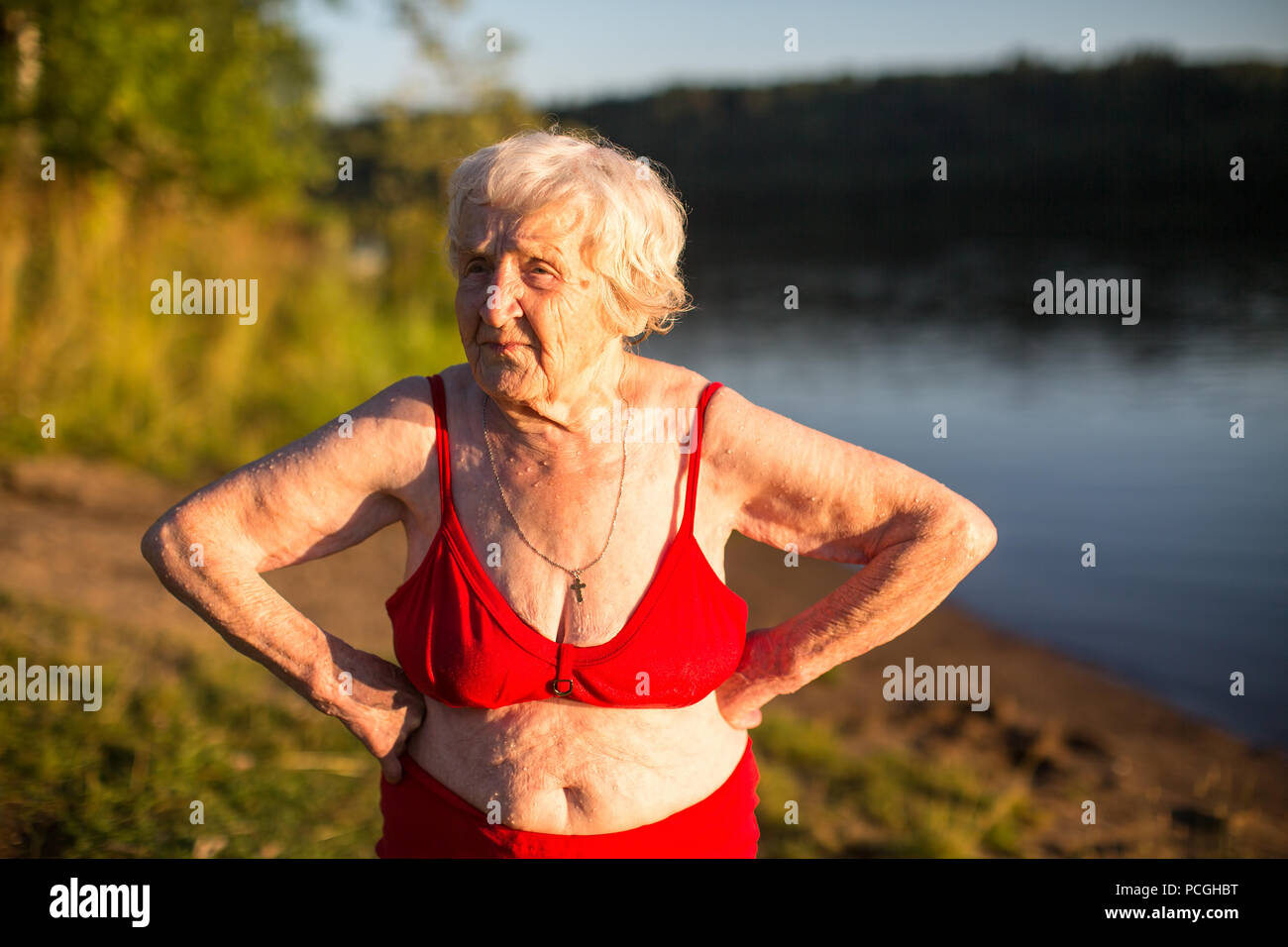 Elderly woman in a swimsuit is on the river bank. - Stock Image