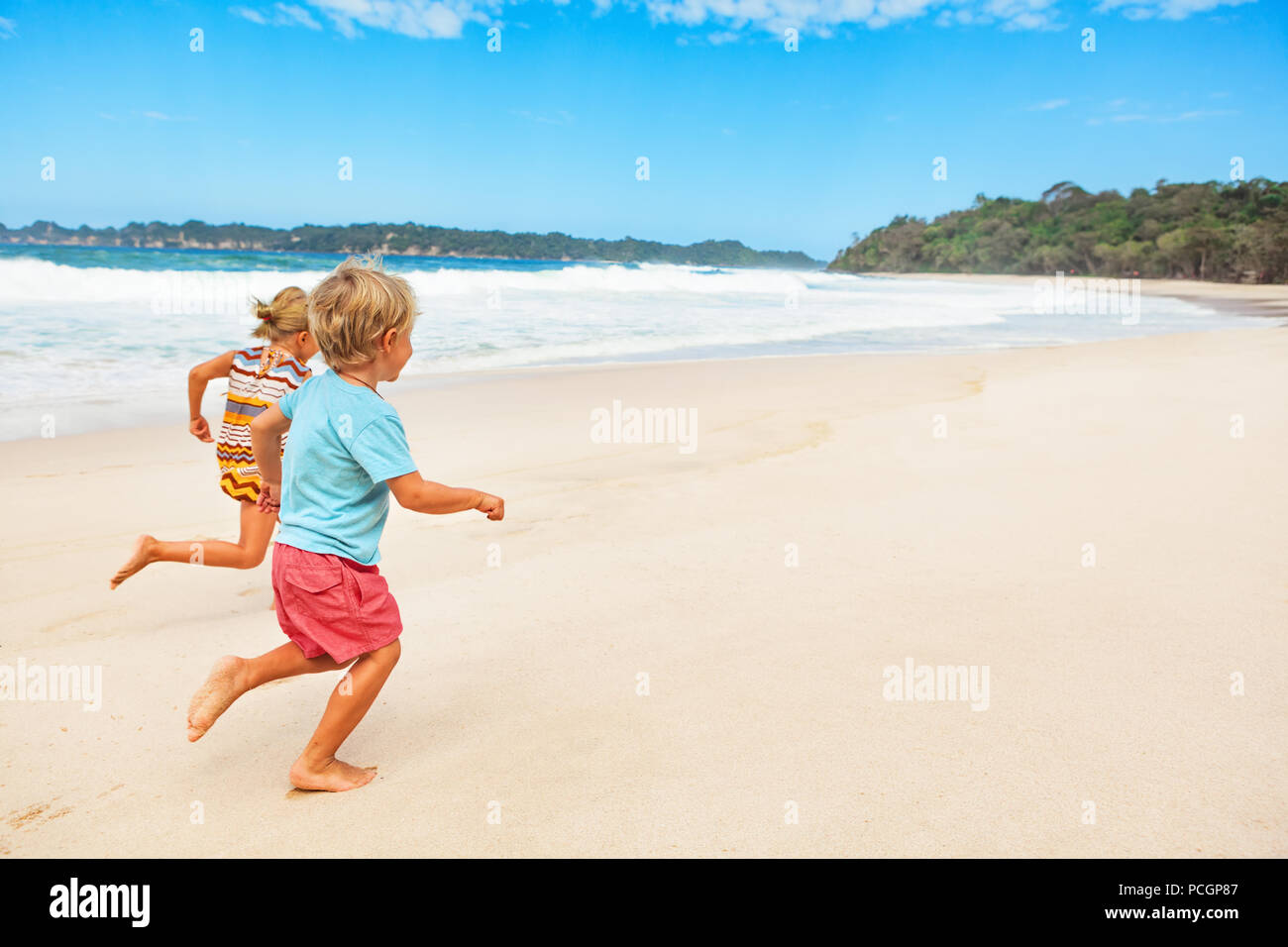 Happy barefoot kids have fun on beach walk. Run and jump by white sand along sea surf. Family travel lifestyle, outdoor sports activities and games. - Stock Image