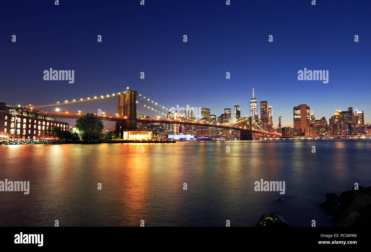 Panorama of Brooklyn Bridge and New York City (Lower Manhattan) with lights and reflections at dusk, USA Stock Photo