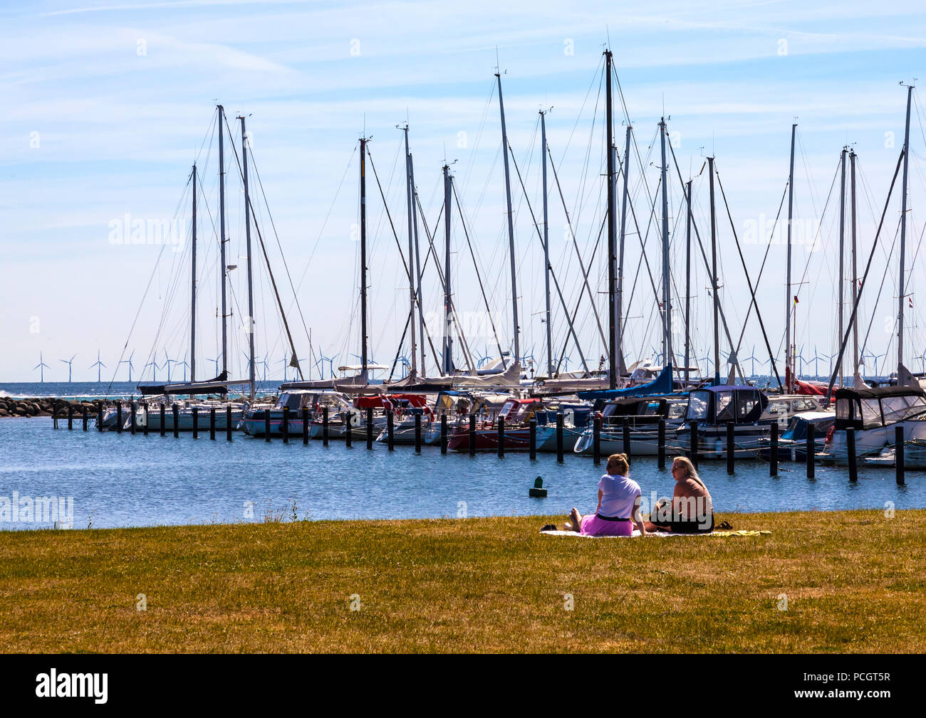 Two women sit and admire moored yachts at Dragør fishing village near Copenhagen in Denmark with wind farm in background - Stock Image