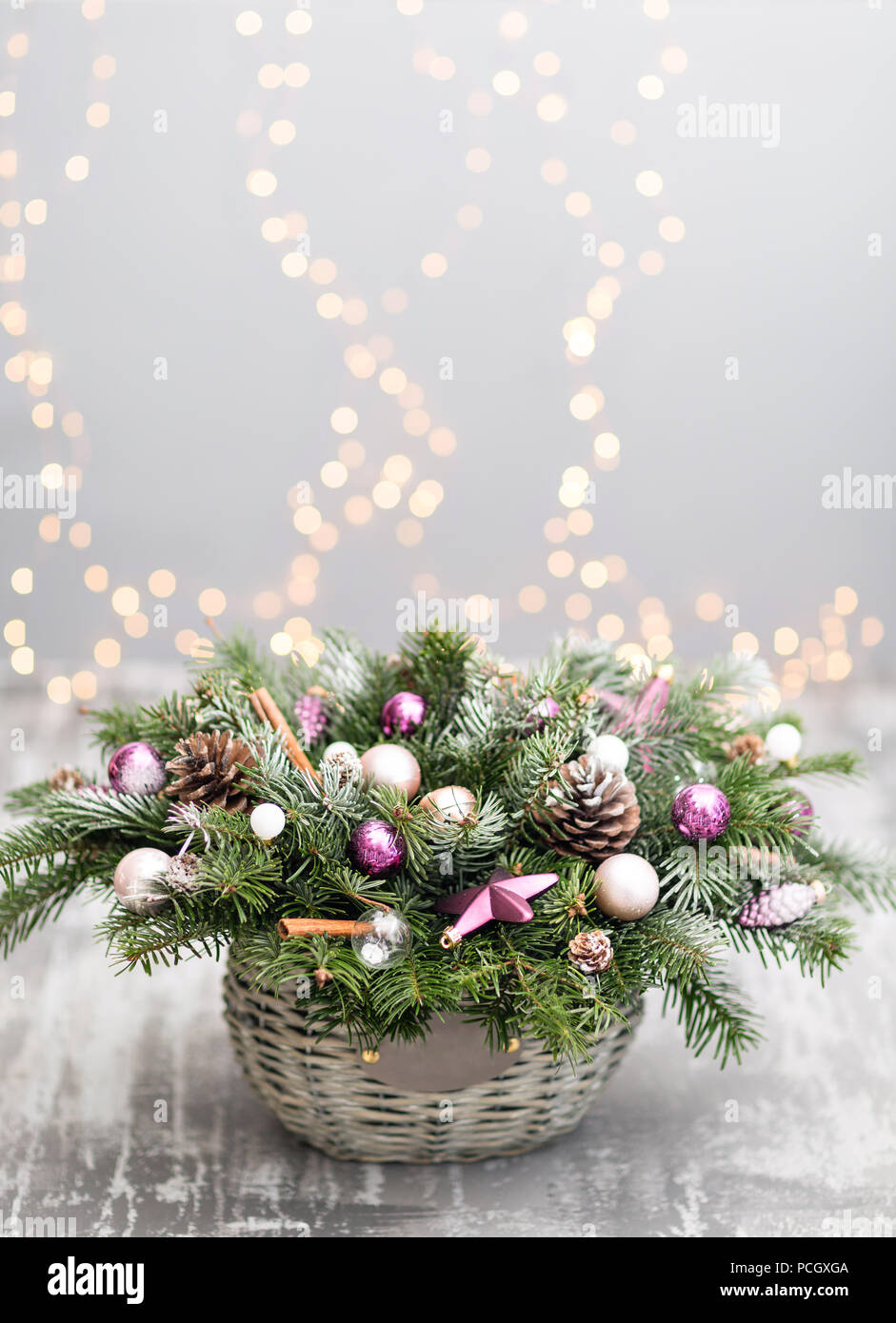 christmas or new year greeting card with a wicker basket with pine cones fir branches decorative balls on old wooden background