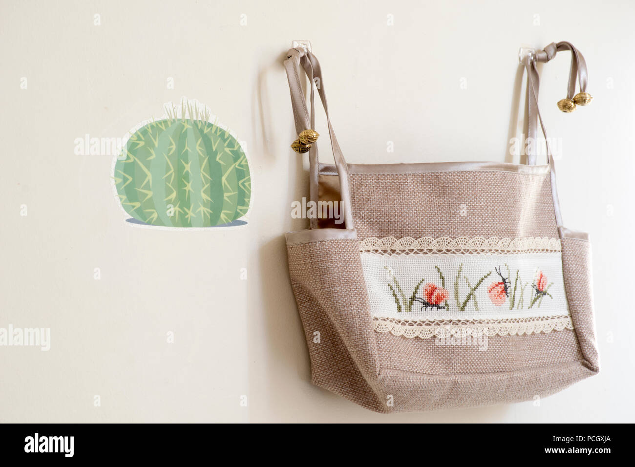 a beautiful handmade bag with a lovely embroidered pattern hung on the wall, used as a crafting bag. - Stock Image