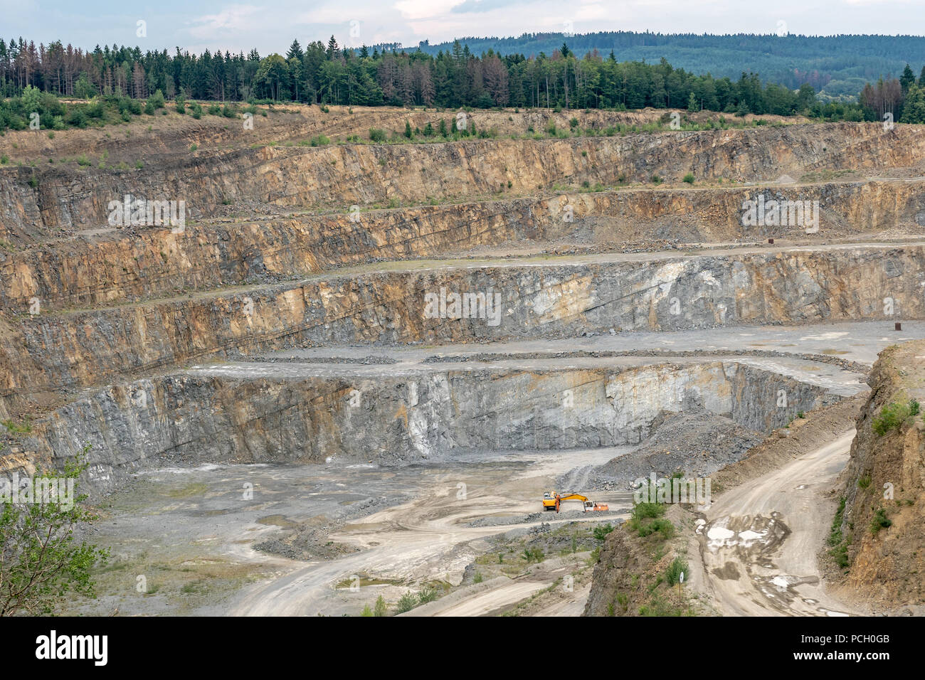 Opencast mining quarry with machinery. Quarrying of stones for construction works. Mining industry in quarry. Stock Photo