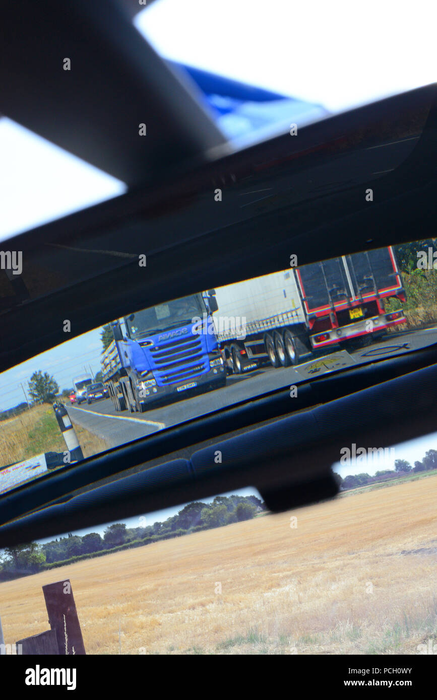 lorry travelling on dual carriageway reflected in vehicle rear view mirror uk Stock Photo