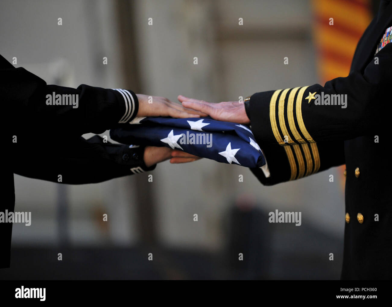 PACIFIC OCEAN (Nov. 16, 2012) Religious Programs Specialist 3rd Class Zachary Misner, left, and Capt. Michael Donnelly, the executive officer of the aircraft carrier USS Nimitz (CVN 68), perform a passing of the flag ceremony during a burial at sea aboard Nimitz. Nimitz recently completed the ship's joint task force exercise, intended to test a strike group's ability to operate in hostile and complex environments with other U.S. and coalition forces. - Stock Image