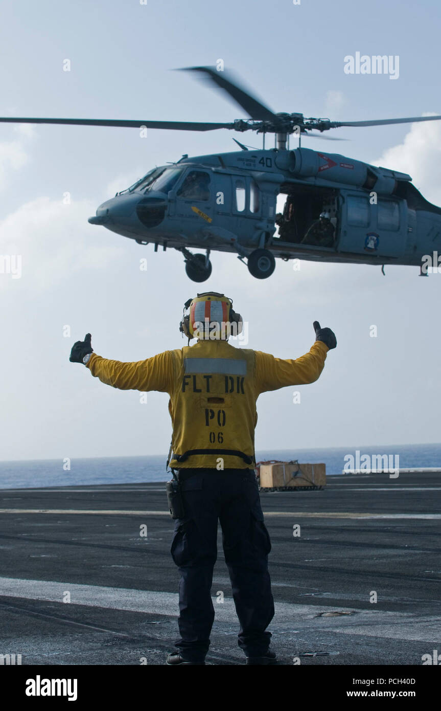 A U.S. Navy aircraft director signals to an MH-60S Knight Hawk with Helicopter Sea Combat Squadron (HSC) 23 during a vertical replenishment at sea with the fast combat support ship USNS Bridge (T-AOE 10) on the flight deck of aircraft carrier USS Carl Vinson (CVN 70) in the Pacific Ocean Dec. 22, 2011. The Carl Vinson and Carrier Air Wing (CVW) 17 were under way on a Western Pacific deployment. - Stock Image