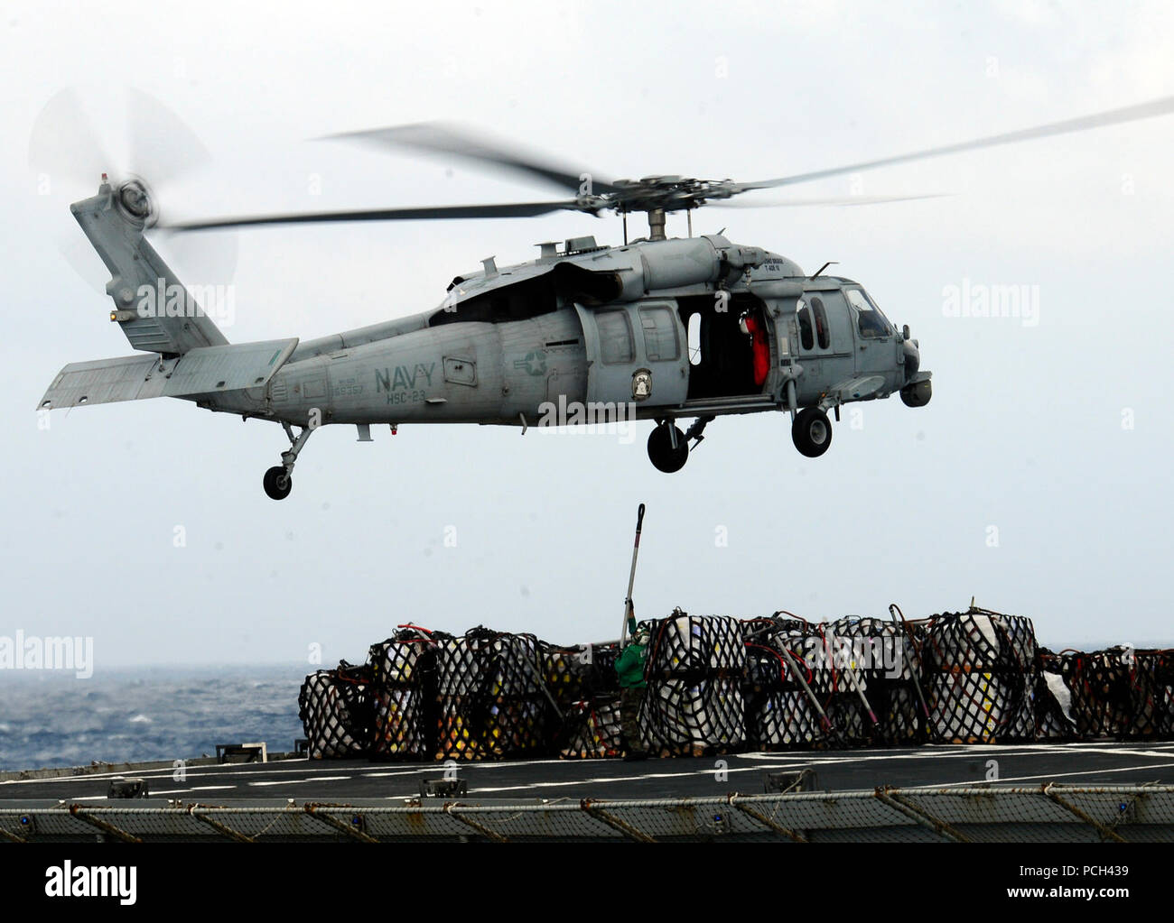 A U.S. Navy MH-60S Knighthawk helicopter transfers supplies from fast combat support ship USNS Bridge (T-AOE 10) to aircraft carrier USS Carl Vinson (CVN 70) during a vertical replenishment Jan. 2, 2012, in the Pacific Ocean. Vinson and Carrier Air Wing (CVW) 17 were under way on a western Pacific deployment. - Stock Image