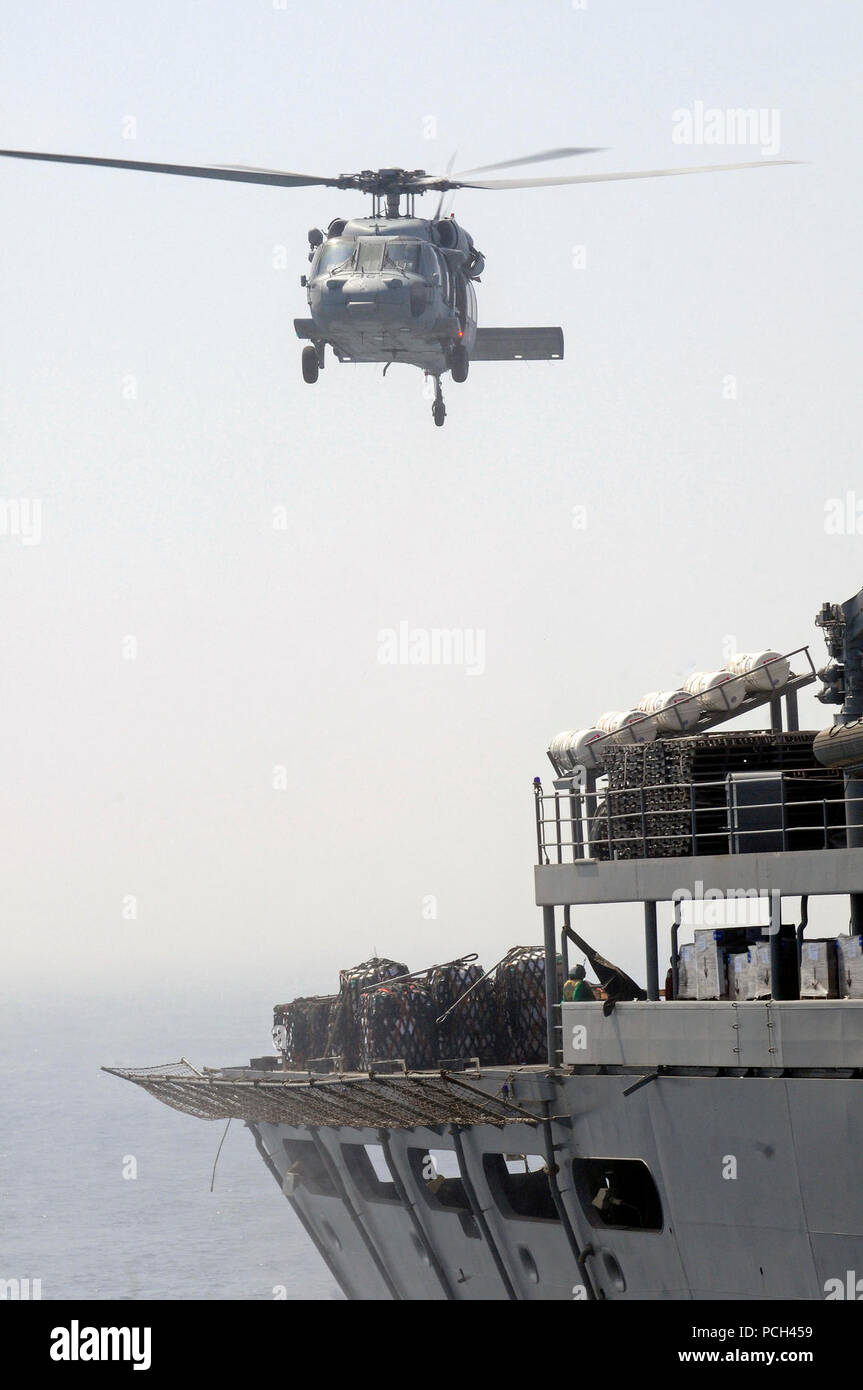A U.S. Navy MH-60S Seahawk helicopter, assigned to Helicopter Sea Combat Squadron (HSC) 23, prepares to pick up supplies from the Military Sealift Command fast combat support ship USNS Bridge (T-AOE 10) during a vertical replenishment with the amphibious dock landing ship USS Comstock (LSD 45) in the Persian Gulf May 17, 2011. Comstock is under way supporting maritime security operations and theater security cooperation efforts in the U.S. 5th Fleet area of responsibility. - Stock Image