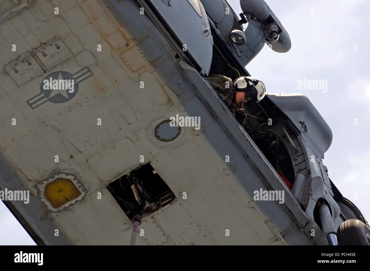 A U.S. Navy naval air crewman checks to see that an MH-60S Seahawk helicopter assigned to Helicopter Sea Combat Squadron (HSC) 23 is clear of the flight deck during a vertical replenishment between Military Sealift Command fast combat support ship USNS Bridge (T-AOE 10) and amphibious dock landing ship USS Comstock (LSD 45) in the Persian Gulf May 17, 2011. Comstock was under way supporting maritime security operations and theater security cooperation efforts in the U.S. 5th Fleet area of responsibility. - Stock Image