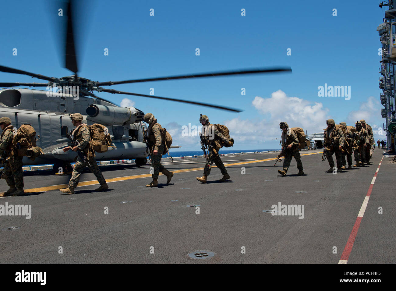 Marines assigned to the 3rd Battalion, 3rd Marine Regiment, board a CH-53E Super Sea Stallion helicopter, assigned to Heavy Marine Helicopter Squadron 463 (HMH-463), on the flight deck of the amphibious assault ship USS Peleliu (LHA 5) during Rim of the Pacific (RIMPAC) Exercise 2014. Twenty-two nations, 49 ships and six submarines, more than 200 aircraft and 25,000 personnel are participating in RIMPAC from June 26 to Aug. 1 in and around the Hawaiian Islands and Southern California. The world's largest international maritime exercise, RIMPAC provides a unique training opportunity that helps  - Stock Image