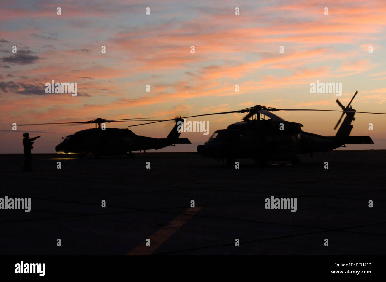 Aircrew directs Navy helicopters at U.S. Naval Station Guantanamo Bay airfield as the sunsets, Jan. 19. The aircraft is part of Fleet Logistics Squadron VRC-40 deployed in support of Operation Unified Response, providing humanitarian assistance to Haiti. Stock Photo
