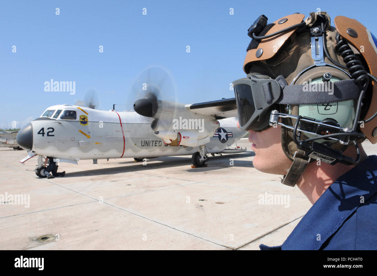 Navy Airman Michael Megyesi, an aviation electronic technician, conducts preflight communications check while a C-2 Greyhound aircraft prepares for departure from U.S. Naval Station Guantanamo Bay, Jan. 24. The aircraft is flying humanitarian assistance to Haiti in support of Operation Unified Response. Stock Photo