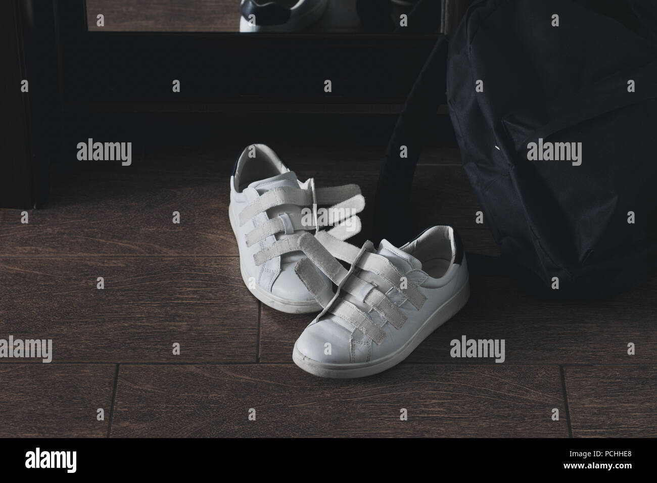 Pair of white shoes on velcro with a backpack close-up - Stock Image
