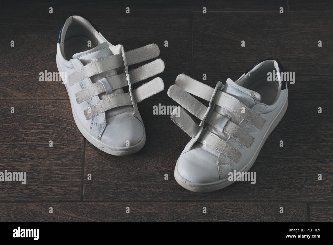 Pair of white, worn-out shoes on velcro, close-up - Stock Image