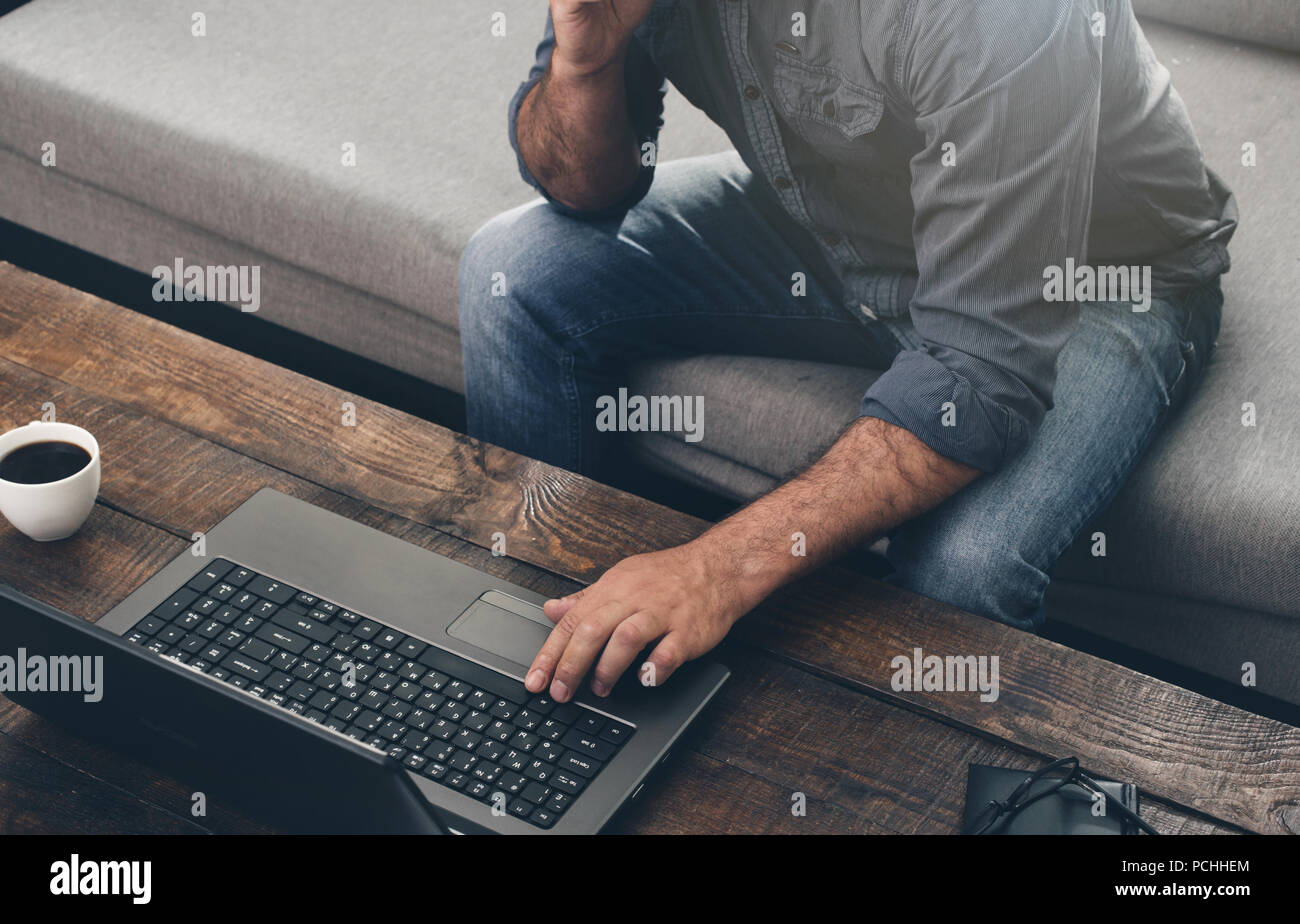 Men hands typing text on the laptop keyboard. Businessman working with laptop at home office. - Stock Image