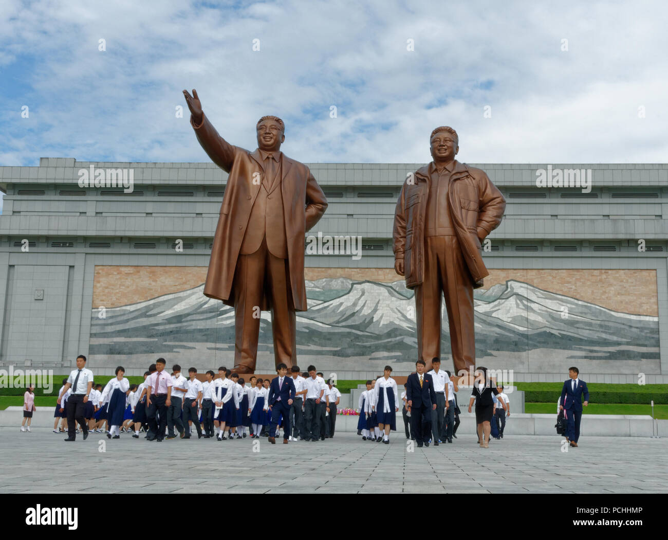 Orderly School children at Mansu Hill Grand Monument two large bronze statues of Kim Il-sung and Kim Jong-Il revered by people Pyongyang, North Korea - Stock Image
