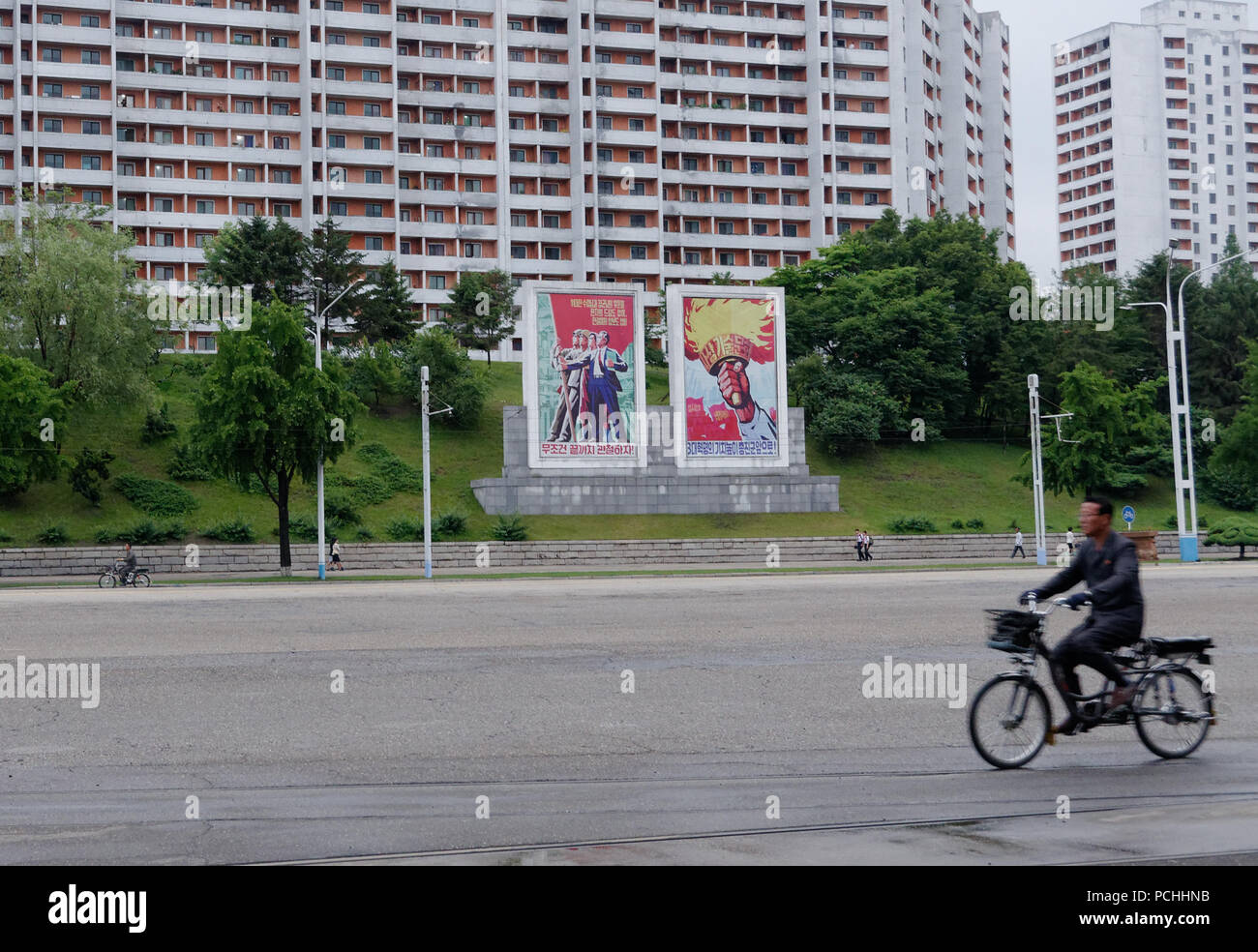 Cyclist passes the inspiration posters that abound in Pyongyang streets across an empty road, North Korea - Stock Image