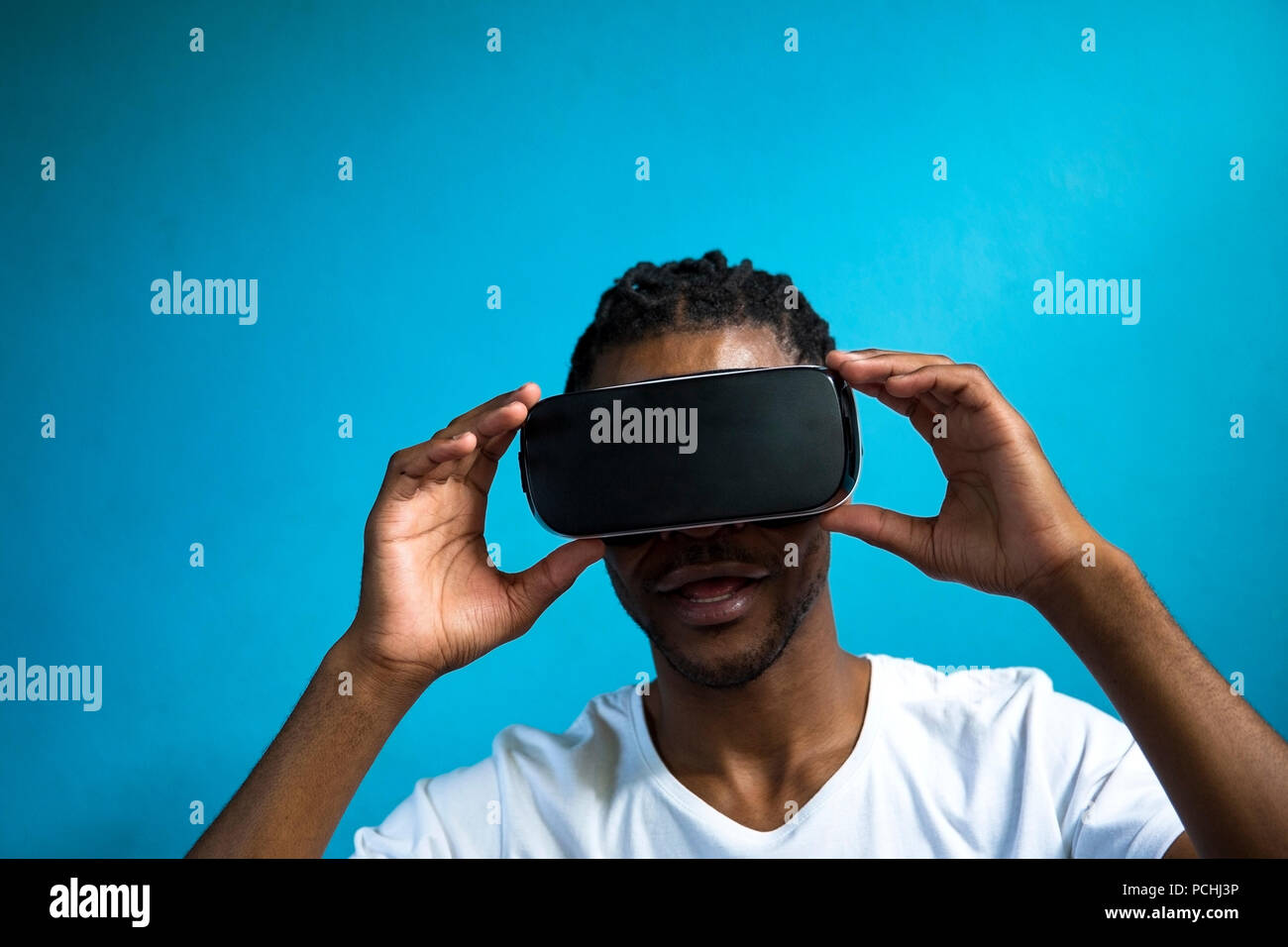 African man looking through VR headset - Stock Image