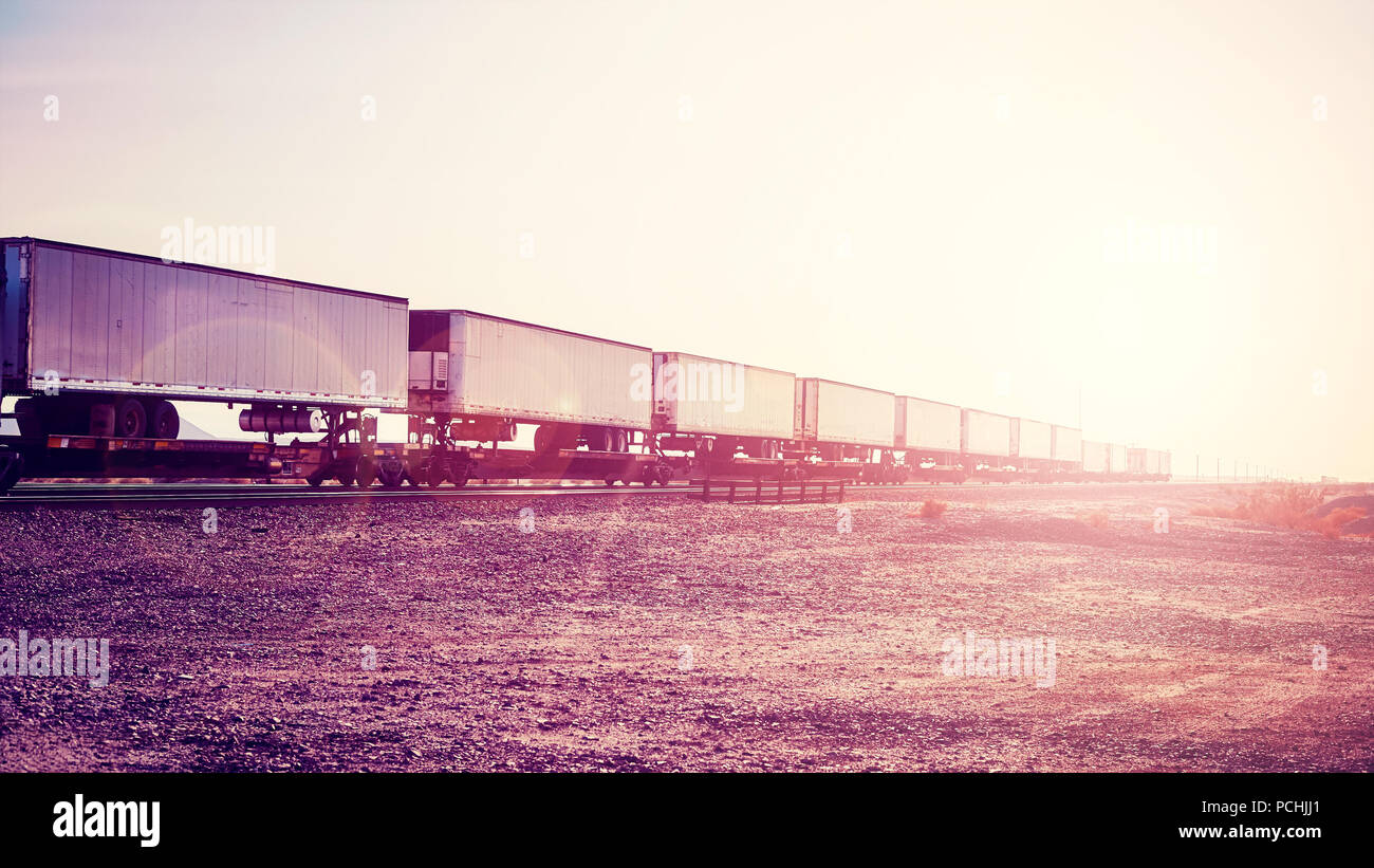 Intermodal freight transport, semi trailers on train at sunset, color toned picture, USA. - Stock Image